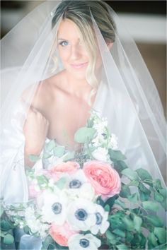 A beautiful bride wearing her wedding veil and carrying her pink garden rose and white anemone garden inspired bouquet at her Bonita Bay Club wedding in Florida | Lana Ponomarenko Photography