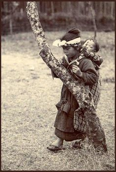 Meiji era / Japan. Young Japanese girl carrying baby on her back.