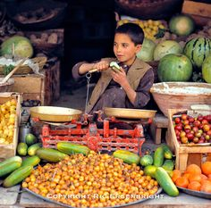 A young boy peels a cucumber in a produce stall in the bazaar at Mazar-i-Sharif, Afghanistan. ©Ric Ergenbright
