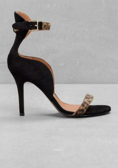 Crafted from suede, these statuesque sandals feature curved, fluid shapes and a thin, tall heel.