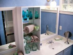A simple vanity was given a vertical uplift with a narrow, glass storage cabinet. Sans doors, this unit provides the ideal place to store decorative jars and linens.
