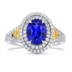 A superb oval sapphire and diamond ring, mounted in Platinum and 18K yellow gold. The ring is set with an oval Blue (heated) Sapphire, and designed with two halos, a split shank and Fancy Vivid Yellow round brilliants