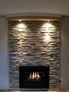Cappella fireplace insert modern style with Placer Gold ledge stone with a soffit with lights .