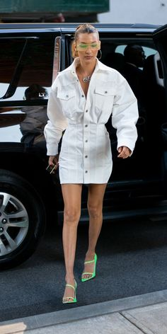 Bella Hadid stunted in a head-to-toe Fenty look, which included a white denim dress and matching neon glasses and pointed-toe sandals. A fancy pendant necklace by Nigora Tabayer completed her winning outfit. Source by sydnesummer dress Denim Dress Outfit Summer, White Denim Dress, Sleeveless Denim Dress, Denim Outfit, Jeans Dress, Summer Outfits, Denim Dresses, Swag Dress, Dress Shoes
