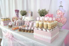 Mesa de dulces decorada en tonos blanco y rosa.