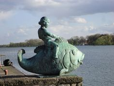 This is a small statue located at the waterside of the Maschsee near to the small marina in Hannover, Germany, Niedersachsen. It is named 'Putte auf dem Fisch'.