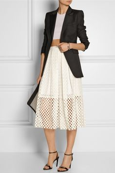 White eyelet knee length skirt, black half sleeve blazer, white cropped top, black open toed heels, and a cream and black large clutch purse.