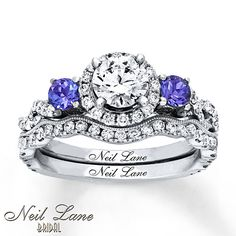 This dazzling bridal set from Neil Lane Bridal® is a vibrant ode to Hollywood glamour. A stunning round diamond at the center of the engagement ring is framed in additional round diamonds and flanked by breathtaking round tanzanites. More round diamonds interweave along the band of the engagement ring and flow along the contoured matching wedding band. The bridal set is styled in 14K white gold and has a total diamond weight of 1 1/3 carats. Neil Lane's signature appears inside each ...