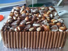 Chocolate cake with chocolate fudge filling, fudge topping, covered in Guylian chocolates and enclosed in chocolate fingers.