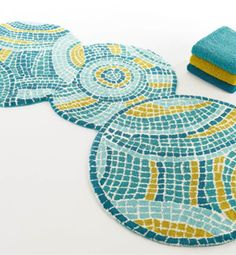 The Park Rug by Abyss & Habidecor. This new rug was designed to mimic the appearance of a tile pattern. Three large circles, of complementary blue and olive shades, create a unique piece for your home. Large enough to use in an entry way or guest room.