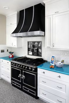 Description of . The remodeled kitchen's arctic-white walls, cabinetry and tile backsplash beautifully frame the ebony La Cornue range and hood. Bernard Andre Photography.