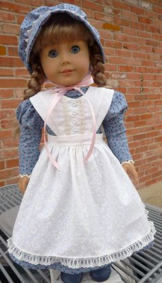 This outfit has been made to fit 18 dolls such as American Girl, Battat, Madame Alexander, Journey Girls and more.    American girl Kirsten is modeling this pretty prairie outfit for us. The dress is a modified Keepers pattern made from a blue calico print. I put cluny lace at the neck and wrists. The back of this dress closes with snag-free Velcro. The length of the dress is mid-calf. The pinafore is made from a white on white floral print fabric. It is part of the newest Keepers Civil War…