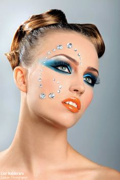 Crystals accent stunning blue and orange eye shadow with orange lips.