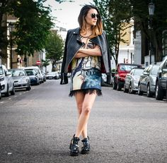 Anisa Sojka wearing black round Le Specs Ziggy sunglasses, yellow Pocket London by Max De Courey Basketball Kurt Vest, black peacock feather Aqua skirt, black Oui leather jacket and black cut-out River Island boots. Street style taken in London.