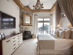 The stone corner fireplace and wood beamed ceiling more than make up for the size of the master bedroom White Houses, Hamptons House, Rustic Master Bedroom, Luxury Homes, House, Home, Home Bedroom, Home Decor, Corner Fireplace