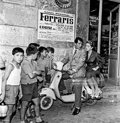 American actor Dean Martin (Dino Paul Crocetti), is on board a Vespa with Italian/born American actress and soprano Anna Maria Alberghetti while a group of children watching them curiously. Rome, 1957