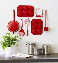 Take those old or unused kitchen accessories, give them a bright coat of spray paint and use them as wall decor!