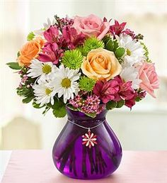 1-800-Flowers® Mothers Devotion™ with Charm  EXCLUSIVE A truly original gift that lets Mom know you're devoted to her without a doubt. A rich bouquet of peach roses, pink roses, alstroemeria and poms, hand-arranged in a stunning purple vase, is paired with our exclusive blossom pendant and necklace that will keep her smile blooming for years to come. As Shown $64.99