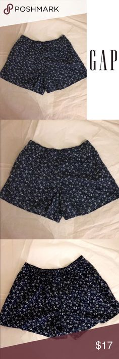"""NWT Gap Kids Flowy Shorts in Navy Blue These new with tag shorts are perfect for a hot day. They are really light and not tight, making the shorts extremely comfortable. The color of the shorts is a navy blue, with a white flower pattern. These shorts are in a Gap Kids girl's size large, which is a size 10, age 9-10, 73-81 lbs., 54-57"""" height, 24"""" waist, and 30"""" hip. GAP Bottoms Shorts"""