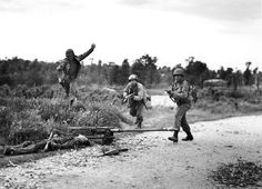 This is a remarkable, kinetic photograph taken by Fred Ramage in Cherbourg while pockets of resistance were cleared after D-Day. Ramage's back was dangerously toward the German position. Note the soldier at the left holding his pistol while jumping over a corpse as his comrades walk. The dead German was manning a Solothurn S-18/1000 20mm antitank rifle. Of the two rifles visible on the ground, the one nearest the German has its bolt open, suggesting he was killed as he tried to chamber a…