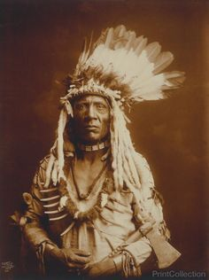 Weasel Tail, Piegan North American Indian, photographed by Edward Curtis in 1900. Half-length portrait, facing front, holding tomahawk.