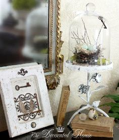 Entry. Cloche with found bird nest, antique books and skeleton key, and mixed media art in whites.