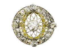Belle Époque diamond cluster ring, circa 1905. Openwork cluster ring set with a round old cut diamond to centre in a rub over setting with an approximate weight of 0.55ct. Set to the outer edge with twenty round old cut diamonds, four of which are in raised rub over settings, with an approximate combined weight of 1.20ct. Platinum topped to a yellow gold intricate gallery and ridged shank.