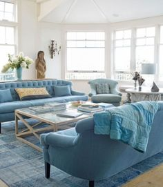Blue removes pretension from formal living areas, as seen in this Martha's Vineyard home. Furnishings are awash in a sea of blues, but slight variations in tone and subtle patchwork motifs take the place of sharply contrasting patterns and hues. A patchwork rug from Nomadic Trading Company anchors the living area, furnished with linen sofas and a wingback chair by Cisco.