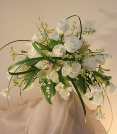 airy free form roses, greens, lemon grass and orchids, makes either a cascade bridal bouquet or can be use on top of a tall vase