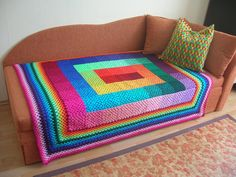 Full Spectrum Granny Square Blanket    Made of 63 different coloured granny squares from burgundy to dark pink across red, orange, light orange, yellow, neon green, mint green, emerald green, dark christmas tree green, teal, turquoise, blue, dark blue, indigo, purple, violet, lilla, baby pink, salmon and neon pink. All these colours are blended in rainbow order starting from the middle creating a swirl and they never repeat!