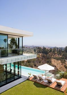 The view from the custom-built infinity pool spans from neighboring canyons to downtown Los Angeles and over to the ocean, and provides the perfect relaxation spot thanks to chaises from RH | archdigest.com