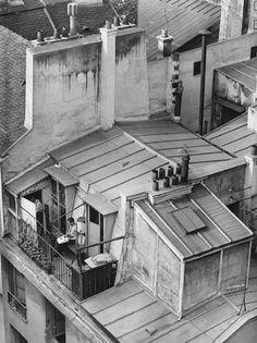 André Kertész; Latin Quarter, Paris (man on rooftop balcony) 1926.