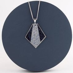 6 More Artisans Who Make Gorgeous Paper Jewelry. This example is a paper and silver pendant necklace by Circle and Dash. #paperjewelry