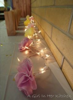These were made by dying white coffee filters in water and food coloring. After drying, I stacked four filters of the same color and pinched them in the middle and tied a twist tie around the pinch. Then I fluffed the flowers and attached them to the lights with their twist ties. It's super easy!