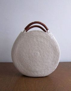 Round white bag made out of cotton rope and up-cycled soft brown leather. This bag is durable and roomy enough to fit all your necessities - measures about 12 inches across and 2 inches deep, with about 3 inch handles. Find a simple cotton rope basket bag Crochet Handbags, Crochet Purses, Crochet Bags, Cotton Rope, Cotton Bag, Round Bag, Round Basket, Sac Week End, Diy Sac
