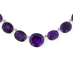 A stunning riviere necklace from the Georgian period. Twenty six vibrant deep hued amethysts are set in backed collet settings which are crafted in silver over 14 karat yellow gold. The oval cut amethysts gently graduate in size towards the center stone which weighs over 16 carats. An antique treasure.