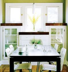 Though this dining room is hardly big enough for a table and four chairs, sleek, glass-front built-in shelves and drawers make use of the space underneath the windows. | myhomeideas.com