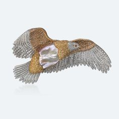 Eagle brooch in white and yellow gold with pearl, white and brown diamonds and ruby eyes. The eagle is the creature that arms Zeus with the thunderbolts that this head divinity hurls against his enemies. Only the eagle's piercing gaze is able to challenge the sunlight. Imposing and imperial, it represents strength, freedom, independence.
