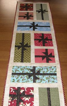 Brighten your Christmas table with this unique quilted table runner. Christmas presents of varying colors and sizes all tied up with a bow. A gold polka dot metallic set on a black background was used for all of the bows. A red and green diagonal stripe to add a fun binding. Use it to add color and texture to your table, kitchen island, coffee table, side board or office credenza. Perfect gift for a newly wed couple. 15 1/2 x 57 Other Christmas items may be found here: https:/&#x...