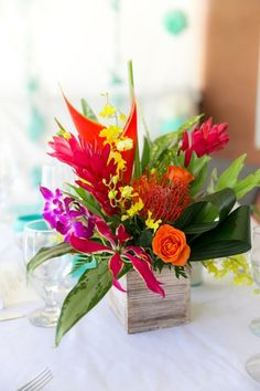 Tropical wedding centerpiece idea - bright colored centerpiece with proteas, roses + orchids in wooden vessel  {Crown Images photography by Sage}
