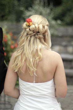Halb hochgesteckte Brautfrisur, locker gebunden und mit einer schönen Rose als Eyecatcher.
