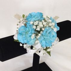 Wrist corsage of ice blue mini carnations with a dainty off-white bow.