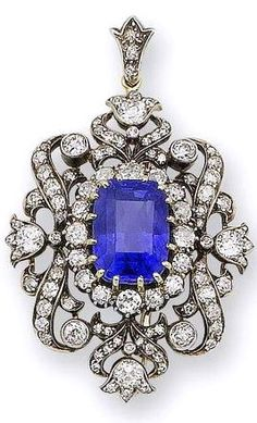 A late 19th century sapphire and diamond pendant/brooch, circa 1890 The central cushion-shaped sapphire, weighing 14.61 carats, and old brilliant-cut diamond cluster within an old brilliant and single-cut diamond border of scroll and floral motifs, suspended from a detachable diamond-set suspensory loop, mounted in silver and gold, diamonds approximately 3.85 carats total, detachable brooch fitting, length 5.5cm.