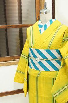 ぱっと目をひく綺麗なイエローに、スプリンググリーンとマンダリンオレンジ、ライムグリーンなどのシトラスカラーで織り出された繊細なチェックとモダンなストライプが形作る幾何学パターンがアートでスタイリッシュなウール単着物です。