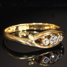 This antique Edwardian diamond 18k gold ring was handcrafted in England around 1910. It is a three-stone glittery diamond ring totaling .3 carats