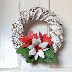 Věneček na dveře Bílý dekorační věnec vyrobený z papírového pedigu, ozdobený perličkovou šňůrou a červenými a bílouvánoční hvězdou se zelenými listy. Na dveřích vykouzlí tu správnou svátečníatmoféru. Věneček je určený do interiéru. Průměr 21 cm.