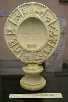A cast of a roman period sundial with the signs of the zodiac around it. It is one of many casts and models in the Museo Della Civilta Romana in EUR, Rome. Here is the text from the label in english: SUN DIAL: the disc-shaped clock is decorated around the edge with a band containing the twelve signs of the zodiac. (Rome, National Roman Museum).