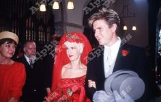 Simon Le Bon walking Paula Yates down the aisle to her wedding to Bob Geldof. Better detail of the daring red gown.