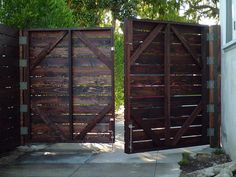 Sightly Wooden Driveway Gates And Comely Entry Way Design Ideas: Pleasureable Dark Brown Finished Old Wooden Driveway Gates With Cement Floors Front Yard Pavers Also Big Trees As Country Front Yard Views