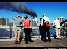 Pedestrians on the waterfront in Brooklyn, New York, look across the East River to the burning World Trade Center towers Sept. 11, 2001 after a terrorist attack.